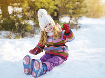 Little child sitting on the snow having fun Stock Image