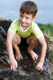 Little child sitting on trunk Stock Images