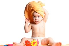 Little child sitting on a white background wrapped in a yellow towel stock image