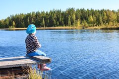Little child sitting on wooden jetty lake front, legs dangling, copyspace Royalty Free Stock Photography