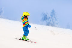 Little child skiing in the mountains in winter Stock Photos