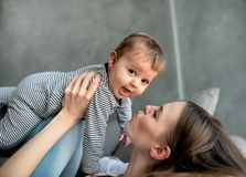 Little child smiling and happy with mom. On the sofa royalty free stock photo