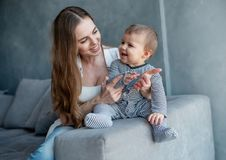 Little child smiling and happy with mom. On the sofa royalty free stock image