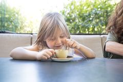 Little child smiling and playing with coffee cup and spoon. Four years old blonde child sitting at the table, playing with coffee cup and spoon, next to woman in Royalty Free Stock Photo