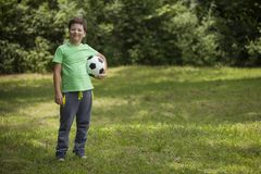 Little child soccer player. Boy with ball on green grass.  Stock Images