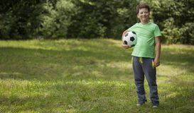 Little child soccer player. Boy with ball on green grass.  royalty free stock photo