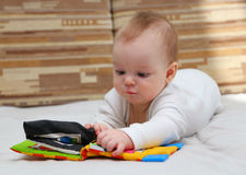 Little child with special baby book. Little child explores special baby book by touching it Stock Photos