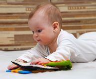 Little child with special baby book. Little child explores special baby book by touching it Stock Images