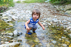 Little child standing in flashy river Royalty Free Stock Photography