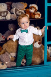 Little child standing on the floor near the Christmas bears in the white shirt and green pants. And tie Stock Photo