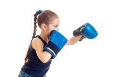 The little child is standing sideways in front of the camera and reaches out his hands in boxing gloves Royalty Free Stock Photo