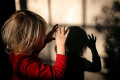 Little Kid Making Shadow Puppets with Fingers on the Wall of her Home royalty free stock photo