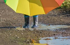 Little child stands with rubber boots in a puddle holding a big umbrella royalty free stock photos