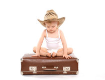 Little child in a straw summer hat sitting on the suitcase Royalty Free Stock Images