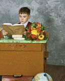 Little child stressed tired leaning on pile of books, stock photography