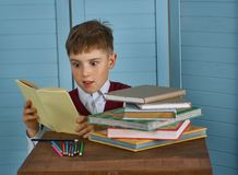 Little child stressed tired leaning on pile of books Stock Photo