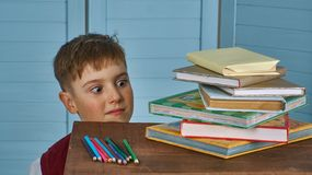 Little child stressed tired leaning on pile of books royalty free stock image