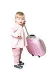 Little child with suitcase. One little child standing with suitcase. Pink clothes and luggage. Isolated on white background Stock Photo