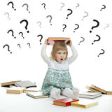 Little child surrounded by books and question marks Stock Photos