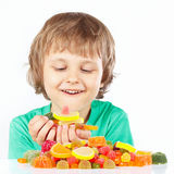 Little child with sweets and jelly candies on white background Royalty Free Stock Image