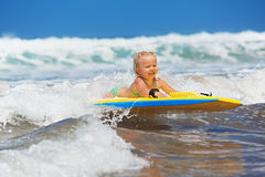 Little child swimming with bodyboard on the sea waves Royalty Free Stock Photography