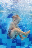 Little child swimming with fun and diving down in pool. Funny photo of baby boy swimming and diving in pool with fun - jumping deep down underwater with splashes Stock Photo