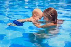 Little child swimming in pool with mother Royalty Free Stock Images