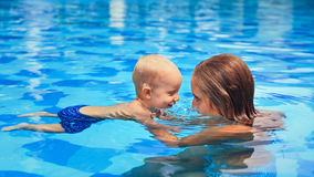 Little child swimming in pool with mother. Happy little sports men has swimming lesson with mother - active baby swim with fun in women hands in swimming pool Stock Photos