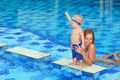 Little child swimming in pool with mother. Little happy sports men in underwater goggles - active baby swim with fun, jump to mother hands in swimming pool Stock Photo