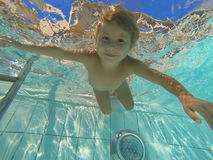 Little child swimming under water in pool Stock Photo