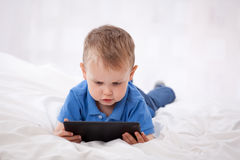 Little child with tablet PC. Little boy uses tablet PC while lying on bed royalty free stock photo