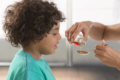 Little child takes spoon of syrup against his cough Royalty Free Stock Photos