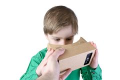 Little child takes virtual reality (VR cardboard)  on white background Stock Photos