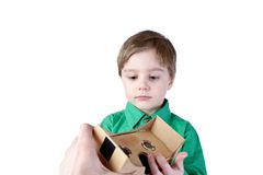 Little child takes virtual reality (VR cardboard)  on white background Royalty Free Stock Image