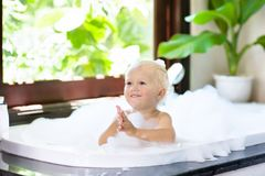 Child in bubble bath. Kid bathing. Baby in shower. Stock Photography