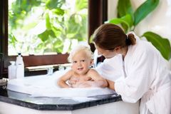 Mother washing baby in bubble bath. Water fun. Little child taking bubble bath in beautiful bathroom with big garden view window. Mother washing baby. Kids Royalty Free Stock Images