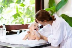 Mother washing baby in bubble bath. Water fun. Little child taking bubble bath in beautiful bathroom with big garden view window. Mother washing baby. Kids Royalty Free Stock Photography