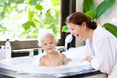 Mother washing baby in bubble bath. Water fun. stock photos