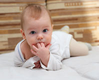 Little child tastes his fingers. Little child lying on the bed tastes his fingers Stock Photos