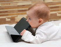 Little child tastes his tablet computer.  Royalty Free Stock Image