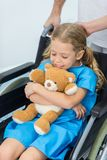 Little child with teddy bear sitting in wheelchair. In hospital royalty free stock image