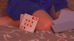 Little child playing with cards. Little child throwing cards on the bed while playing in his room at home stock video footage