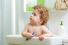Little child with toothbrush sitting inside sink Royalty Free Stock Image