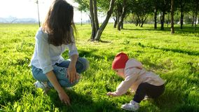 Little child tries to get to his feet and take the first step. Happy young mother with baby sitting in the park on the stock image