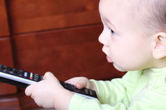 Little child with a TV remote control Stock Photo