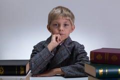 Little child in tweed jacket. Around encyclopedias Royalty Free Stock Image