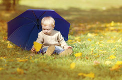 Little child with umbrella in autumn park Stock Image