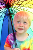 Little Child Under Rainbow Rain Umbrella. A happy little two year old boy child is smiling as he stands outside under a rainbow colored umbrella to keep dry from Royalty Free Stock Images