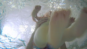 Little child under the water in the child pool. The camera is under the water in the child pool. The father put on the water the little baby. The kid start stock footage