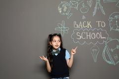 Little child in uniform near drawings with text BACK TO SCHOOL on grey background stock images